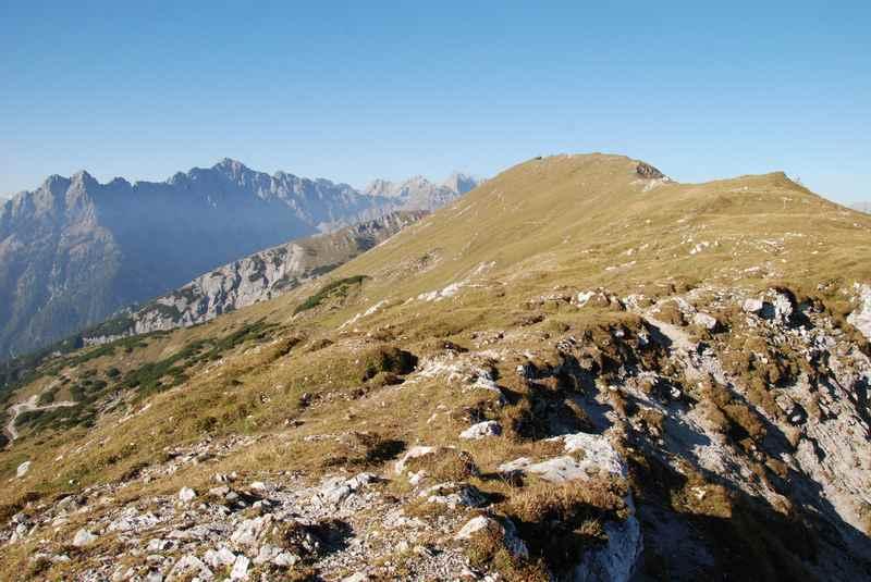 Am Stanser Joch über die Almwiese wandern zum Gipfelkreuz